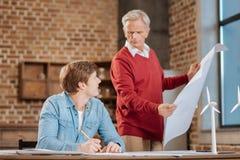 检查他的年轻同事的图纸资深老练的人 免版税库存照片
