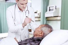 检查他的患者眼睛的美国医生 库存照片
