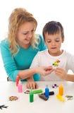 检查他的母亲绘画儿子工作 库存照片