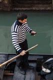 检查他的移动电话的平底船的船夫 免版税库存照片