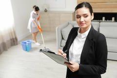 检查佣人工作的家务经理在旅馆里 图库摄影