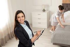 检查佣人工作的家务经理 免版税库存照片