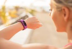 检查健身和健康的妇女跟踪便携的设备 库存照片