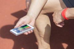 检查健身统计的运动员 免版税库存图片