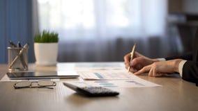 检查公司统计的女性经理,分析收入,特写镜头射击 免版税库存图片