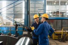 检查关于片剂个人计算机的专家信息在一家现代工厂 免版税图库摄影