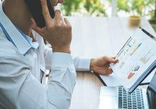 检查关于电话通信的商人报告 免版税库存照片