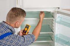 检查冰箱的技术员与多用电表 库存图片