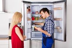 检查冰箱的男性技术员与数字式多用电表 图库摄影