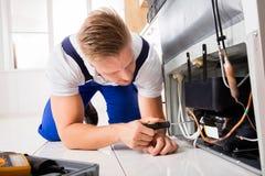检查冰箱的男性技术员 库存照片