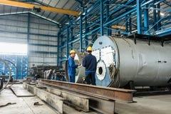 检查制作的锅炉的质量的老练的工作者 免版税库存照片
