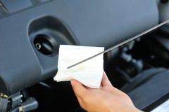 检查发动机油的手 免版税库存图片