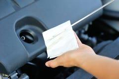 检查发动机油的手 免版税库存照片