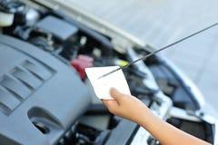 检查发动机油的手 免版税图库摄影