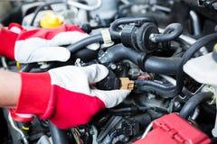 检查发动机电子连接的汽车机械师 免版税图库摄影