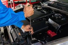 检查和修理在汽车服务车库的技工一辆残破的汽车 库存图片
