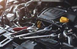 检查和修理在汽车服务车库的技工手一辆残破的汽车 库存照片