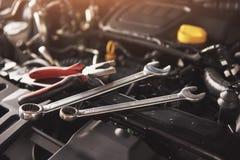 检查和修理在汽车服务车库的技工手一辆残破的汽车 免版税库存照片