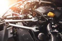 检查和修理在汽车服务车库的技工手一辆残破的汽车 图库摄影