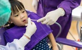 检查和清洗亚洲女孩牙的牙医和助理我们 库存照片