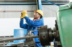 检查在一个工业机器后的工作者质量 免版税库存照片