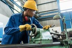 检查在一个工业机器后的工作者质量 库存照片