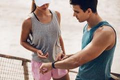 检查在一块巧妙的手表的健身夫妇表现 免版税库存照片