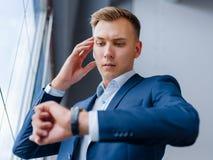 检查在一块手表的繁忙的商人时间在被弄脏的背景 手表辅助部件概念 图库摄影