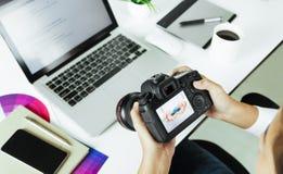 检查在书桌上的摄影师照相机 免版税库存照片