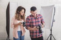 检查在他的照相机份额wi的年轻摄影师照片预览 免版税库存照片