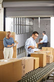 检查在传送带的工作者物品在配给物仓库里 库存照片
