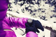 检查在冬天森林和山的妇女远足者体育手表 图库摄影