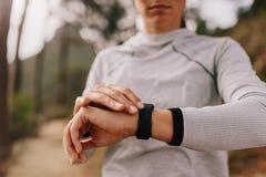 检查在她巧妙的手表的赛跑者健身进展 免版税库存照片