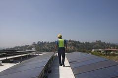 检查在屋顶的维护工作者太阳电池板 免版税库存照片