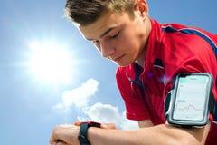 检查在巧妙的手表的青少年的赛跑者设置 免版税库存照片