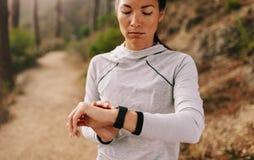 检查在巧妙的手表的年轻健身妇女赛跑者时间 免版税库存图片