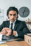 检查在手表的惊奇的商人画象时间,当坐在工作场所时 库存图片