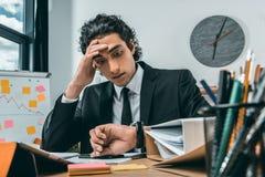检查在手表的疲乏的商人画象时间,当坐在工作场所时 免版税图库摄影
