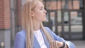 检查在手表的等待的年轻女实业家时间