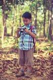 检查在数字照相机的亚裔男孩照片 葡萄酒图片猪圈 库存图片