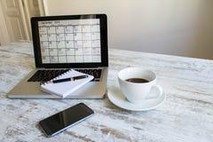检查在日历的月度活动在膝上型计算机 免版税库存照片