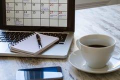 检查在日历的月度活动在膝上型计算机 免版税库存图片
