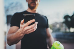 检查在智能手机应用的被烧的卡路里和巧妙的手表的肌肉英俊的运动员在好锻炼会议以后 库存图片
