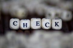 检查在木立方体写的词 免版税库存图片