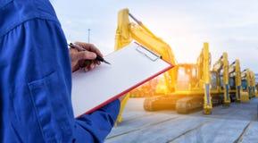 检查在机械挖掘机前面的工作者文件在 库存照片