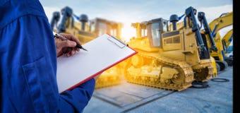 检查在机械挖掘机前面的工作者文件在 免版税库存照片