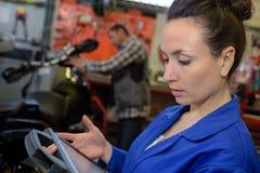检查在汽车修理店的自动女性技工电子系统 库存图片