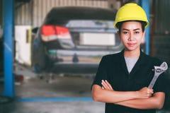 检查在汽车的微笑的年轻女性技工画象  免版税库存图片