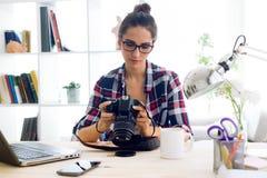 检查在照相机的少妇摄影师预览在螺柱 免版税库存图片
