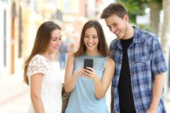 检查在街道的三个朋友智能手机内容 库存图片
